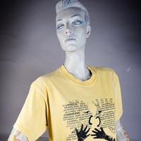"Photo of Elimu T-Shirt on a mannequin. The T-Shirt is yellow with words, in the shape of two people arguing with each other, and has a ""Commesse"" logo on the front."