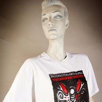 "Photo of Elimu T-shirt on a mannequin. The T-shirt is white and has a black, white and red rectangular design and a ""The Dragon's Mouth"" logo on the front."