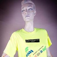 "Photo of Elimu T-Shirt on a mannequin. The T-Shirt is yellow with colourful splashes and has a ""Knot me in dat!"" logo on the front."