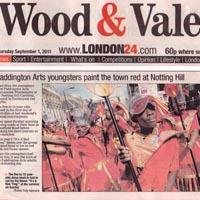 Press cutting about the children from Paddingtion Arts, dressed in red costumes, taking part at the Notting Hill Carnival. A photo of the youngsters in their red outfits is added.
