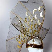 Transparent golden and black headdress with a towering net, embellished with golden moon shapes and small dots.