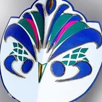 White headdress shaped like a mask with multi-coloured forms on it. The forms look like the face of a bird with a yellow beak in the middle. The other forms are in blue, green or pink and represent circles or curved stripes.