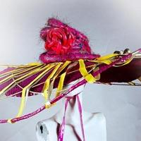 Pink sombrero shaped headdress overlaid with a pink snake-like shape. From there, yellow stripes are hanging and holding a pink rod in front of the face. The headdress is fixed with a knot around the neck.