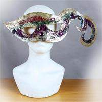 Wide-shaped and curved multi-coloured mask. It has two holes for the eyes in the middle. It is shaped like lips and covered with different colours such as gold, red, green or purple as well as sparkling powder and diamonds on it. On the right side, the mask is formed like two crawls.