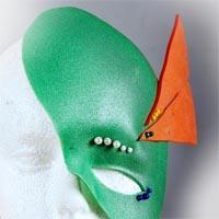 Green mask covering half of the face. There is a hole for the eye, although it is placed beneath the person's eye. Above five small white pearls are placed as well as three small blue pearls beneath the hole. At the place of the ear, an orange triangle with three small yellow and two dark green pearls is fixed.