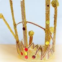 Golden crown with red and yellow buttons on it and a line of little sparkling red stones on the edge of the spikes.