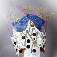 Serrated white crown with black dots and golden stripes on it, overlaid with plastics, golden leafs and blue paper in between the plastics.