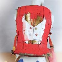 Red backplate with belts at each side of it. In the middle, the plate is coloured in white and brown and there are four buttons which cover the gadget for the backpack.