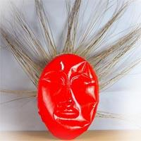 Oval-shaped red plastic mask with very thin hairy bristles stretching in all directions resembling the shape of a sun.