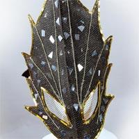 Black long mask with four prongs on each side, occupied with sparkling shardes-similar stones and a golden line along the edges.