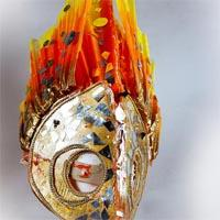 Golden Mask shaped like a falcon cap with orange, red and yellow splashes and shards on it. Orange to yellow flames come out of the top of the mask.