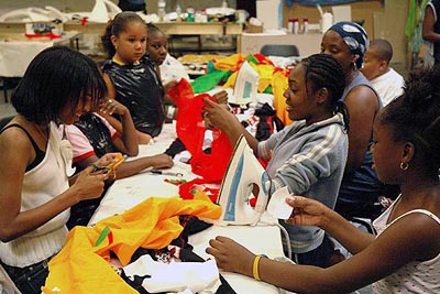 A group of young people sat around a large workshop table. They are variously cutting, shaping, ironing and glueing the pieces of coloured fabric that will become their costumes.